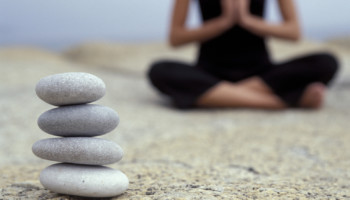 Woman doing yoga by stack of stones